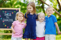 Four excited little kids by a chalkboard Royalty Free Stock Photos