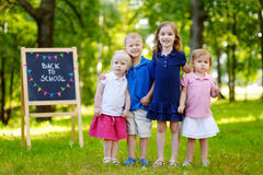Four excited little kids by a chalkboard Stock Images