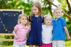 Four excited little kids by a chalkboard Stock Photos
