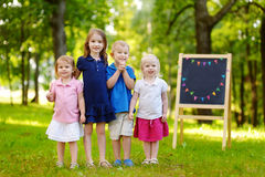 Four excited little kids by a chalkboard Royalty Free Stock Photography