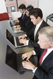 Four executives with laptops. Stock Image