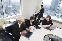 Four executives meeting in a conference room. View of four businesspeople working in an office over laptops on paperwork royalty free stock photo