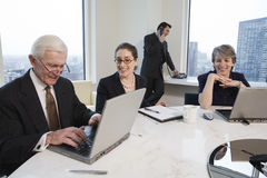 Four executives meeting with laptops in a conferen. View of businesspeople working in an office conference room with laptops. City view in background royalty free stock images