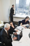 Four executives meeting with laptops in a conferen. Four businesspeople meeting with laptops in a conference room with a city view stock image
