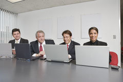Four executives using laptops. Royalty Free Stock Images