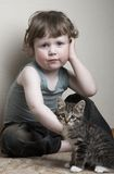 Four eyes. Adorable baby and kitten at home Stock Photos