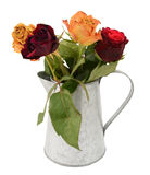 Four faded rose flowers in a metal jug Royalty Free Stock Photography