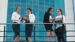 Four fair-skinned business women standing on terrace of office center and discussing their business. Four fair-skinned business women standing on terrace of big stock footage