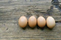 Four Farm Fresh Eggs Aligned on a Farm Table royalty free stock image