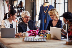 Four Fashion Designers In Meeting Discussing Textiles Royalty Free Stock Images