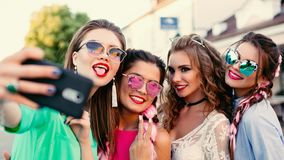 Four fashionable and beautiful best girlfriends in glasses, posing do general self for social networks, lifestyle, spend