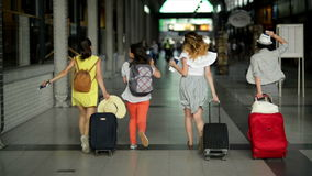 Four female friends in bright summer clothing are late for their plane. Beautiful girls are running inside the airport