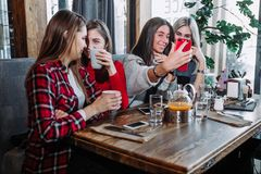 Four female friends enjoying in talking at cafe. Four stylish young women with coffee seated at a table in cafe royalty free stock images
