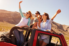Four Female Friends On Road Trip Standing In Convertible Car Stock Photo