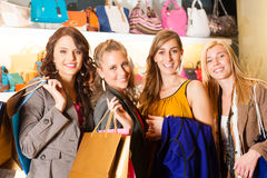 Four female friends shopping bags in a mall. Four female friends with shopping bags having fun while shopping in a mall, leather bags in the background stock photos