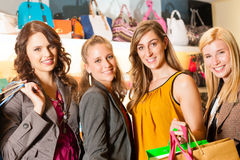 Four female friends shopping bags in a mall. Four female friends with shopping bags having fun while shopping in a mall, leather bags in the background stock images