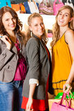 Four female friends shopping bags in a mall. Four female friends with shopping bags having fun while shopping in a mall, leather bags in the background Stock Photography