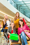 Four female friends shopping in a mall with wheelchair. Four female friends with shopping bags having fun while shopping in a mall, stores in the background; one royalty free stock images