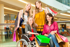 Four female friends shopping in a mall with wheelchair. Four female friends with shopping bags having fun while shopping in a mall, stores in the background; one stock image