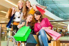 Four female friends shopping in a mall with wheelchair. Four female friends with shopping bags having fun while shopping in a mall, stores in the background; one royalty free stock image