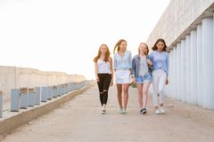 Four female friends walking down at walkway, sunshine background stock photos
