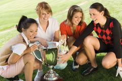 Four female golfers crouching around trophy Royalty Free Stock Photo
