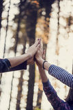 Four female hand joining high up in the air outside in woodland Stock Image