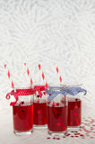 Four festive glasses with red juice and straws Stock Photo