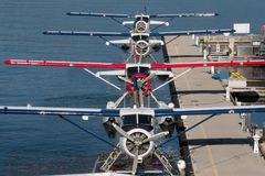 Four float planes are seen in symmetrical formation at their dock in the harbor. Four float planes lie in formation in Vancouver`s harbor extending their royalty free stock image
