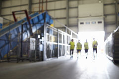 Four figures walking in an industrial interior, soft focus Royalty Free Stock Photos