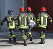 Four firemen in action carry a stretcher with injured Royalty Free Stock Photography