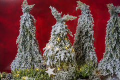 Four firs - one with a light chain against a red background Stock Images