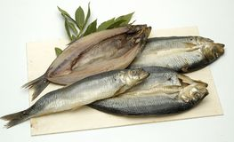 Four Fish. Four whole fish are layered on rectangular platter with green garnish Stock Photo