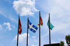 Four flags waving in the sky in Downtown Montreal, Canada. stock images