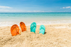 Four flip-flops. Travel background with two pair of orange and green flip-flops in the sand of a beautiful beach, Le Morne, Maurtius, Africa royalty free stock photo