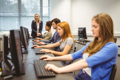 Four focused students with teacher at the end of the class Royalty Free Stock Image