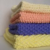 Four folded knitted blankets on a pile royalty free stock photos