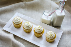 Four French Vanilla Cupcakes and milk in bottle glass Royalty Free Stock Photography