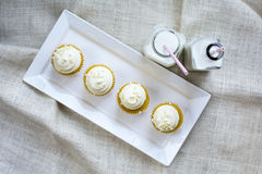 Four French Vanilla Cupcakes and milk in bottle glass stock photo