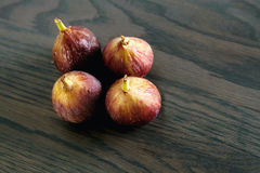 Four fresh brown figs on a gray wooden table Stock Photography