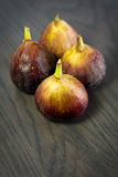 Four fresh brown figs on a wooden gray table Stock Image