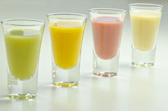 Four fresh and colourful fruit smoothies Stock Photos