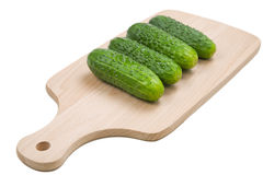 Four fresh green cucumbers on cutting board Stock Images