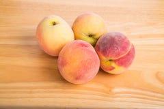 Four Fresh Peaches on a Wood Table Stock Photos