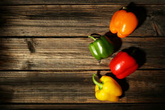 Four fresh pepper on the brown wooden background Royalty Free Stock Photo
