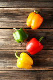 Four fresh pepper on the brown wooden background Royalty Free Stock Photos