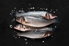 Four fresh raw fish with salt. On the black stone table Royalty Free Stock Photos
