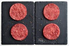Four fresh raw Prime Black Angus beef burger patties Stock Photo