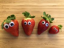 Four fresh red strawberries with googly eyes stock images
