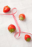 Four fresh strawberries on linen with a ribbon Royalty Free Stock Photo